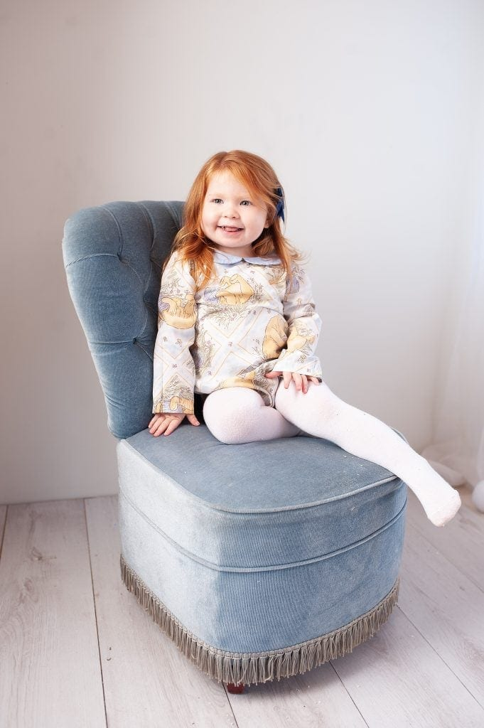 london, kent photographer, red head, winnie the pooh, blue, button back chair, handmade romper, girl, childrens portraits, kids photos, ginger