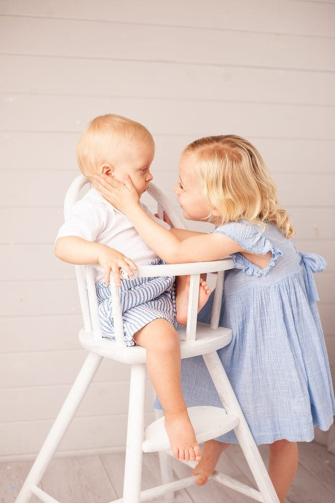 Sibling Love, brother and sister, white highchair, blue dress, next, pinstripe shorts, blonde, natural photos, kids pictures, beckenham, bromley