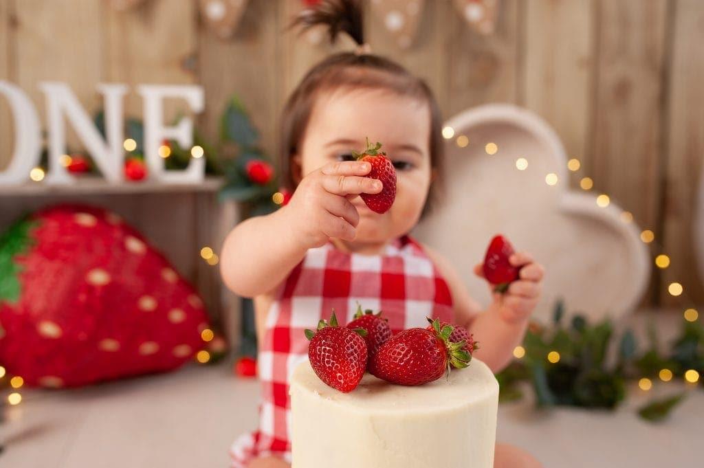 strawberries, heart bowl, wooden backdrop, red check romper, handmade, fairy lights, first birthday cake smash, chislehurst, kent