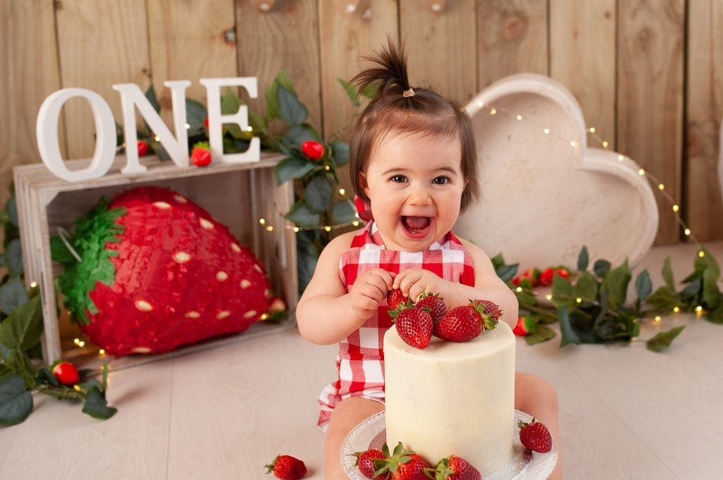 happy girl, wooden backdrop, heart bowl, strawberry vines, strawberry cake, cake smash photographer, bromley, kent